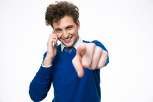 Happy business man talking on the phone and pointing at camera