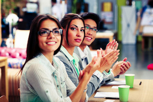 Happy business people applauding in a meeting. Business concept.