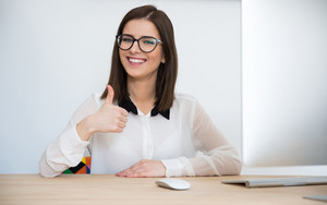 Happy business woman sitting at the table with thumb up