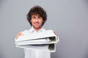 Happy businessman giving folders at camera