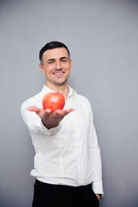 Happy businessman holding apple on palm over gray background and looking at camera