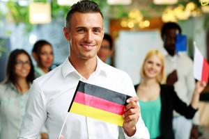 Happy businessman holding flag of Germany in front of colleagues