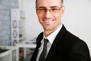 Happy businessman in glasses standing at office