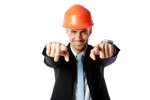 Happy businessman in hard hat pointing at you over white background
