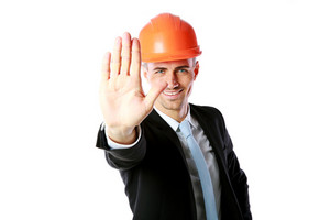 Happy businessman in helmet showing stop gesture over white background