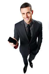 Happy businessman showing blank smartphone screen isolated on a white backgorund