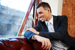 Happy businessman sitting and looking in window at office