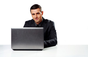 Happy businessman sitting at the table with laptop isolated on a white background