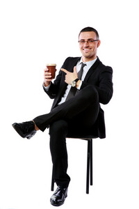 Happy businessman sitting with cup of coffee over white background