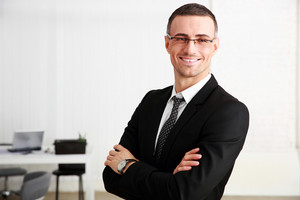 Happy businessman standing with arms folded at office