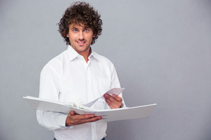 Happy businessman standing with folder