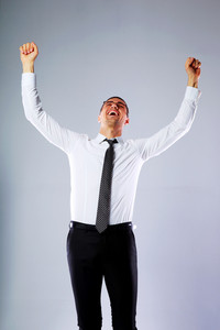 Happy businessman standing with hands raised up over gray background