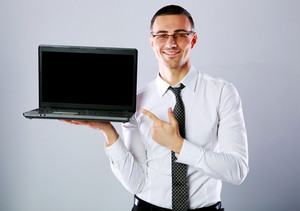 Happy businessman standing with laptop and showing on it over gray background
