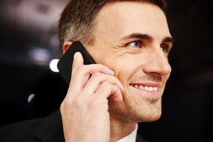 Happy businessman talking on the phone at office