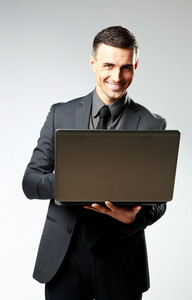 Happy businessman using laptop on gray background