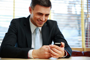 Happy businessman using smartphone at office
