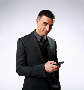 Happy businessman using smartphone over gray background