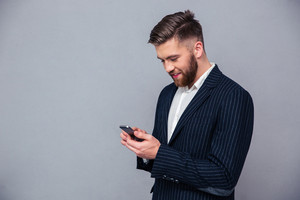 Happy businessman using smartphone