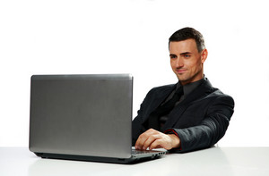 Happy businessman working on laptop isolated on a white background