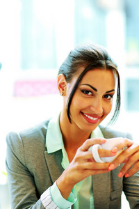 Happy businesswoman holding cup of coffee