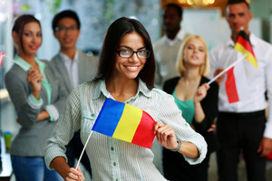 Happy businesswoman holding flag of Romania in front of colleagues