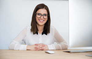 Happy businesswoman in glasses sitting at the table in office