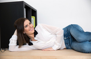 Happy businesswoman lying on the table in office