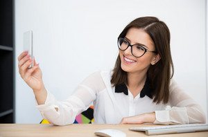 Happy businesswoman making selfie photo in office