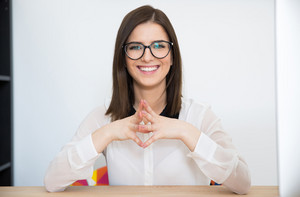 Happy businesswoman sitting at the table in office