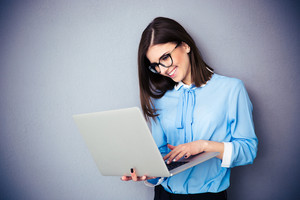 Happy businesswoman standing and using laptop over gray background. Wearing in blue shirt and glasses