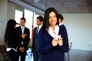 Happy businesswoman using smartphone with colleagues on background