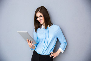 Happy businesswoman using tablet computer over gray background. Wearing in blue shirt and glasses