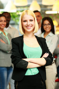Happy businesswoman with arms folded standing in front her colleagues