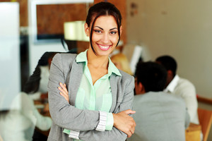 Happy businesswoman with arms folded standing in front of colleagues