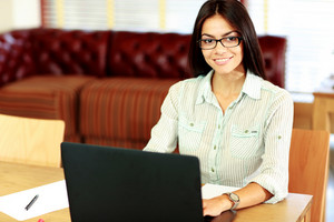 Happy businesswoman working on the laptop at office