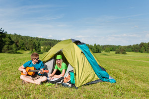 Happy camping couple play guitar outside tent backpack sunny countryside