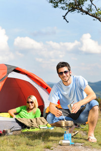 Happy camping couple with tent backpack cooking in sunny countryside