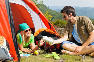 Happy camping couple with tent backpack in sunny countryside