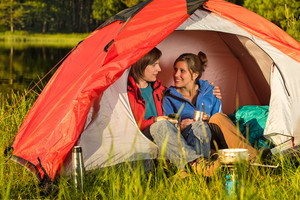 Happy camping teenagers sitting and embracing in tent