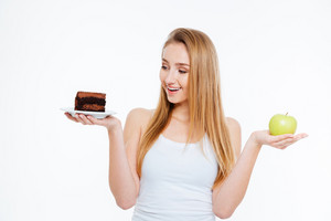 Happy charming young woman standing and holding chocolate cake and green apple over white background