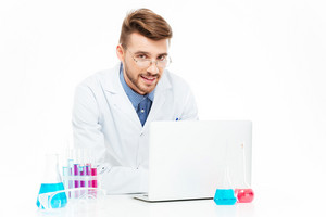 Happy chemist using laptop computer in laboratory