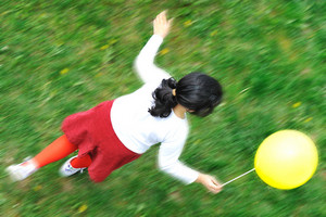 happy child in nature outdoor, little girl running with a balloon in hand