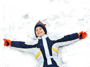 Happy child lies on snow ground