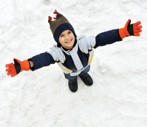 Happy child standing on snow with open arms