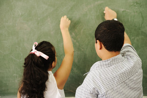 Happy children in classroom, writing on board