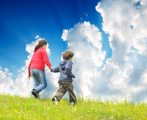 Happy children running on madow with beautiful sky against them