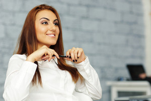 Happy confident relaxed businesswoman in office environment