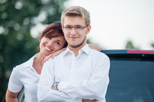 Happy couple posing by a car smiling