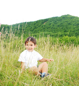 Happy cute kid is sitting on green ground outdoor