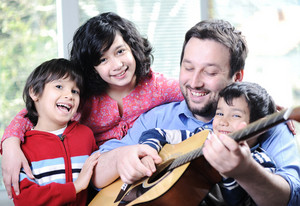 Happy family playing guitar together at home